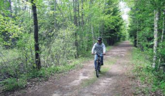 Man riding bike on trail in forest