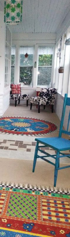 Colorful rugs and chairs on the deck of a house