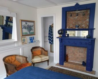 Blue fireplace with orange chairs nearby.