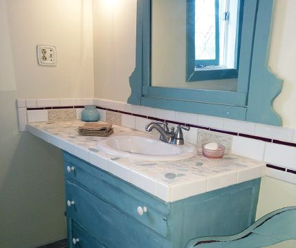Pale blue cabinet and mirror in bathroom.