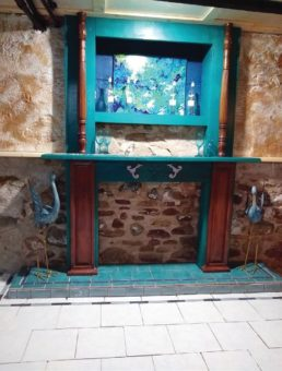 Teal mantel against a stone wall