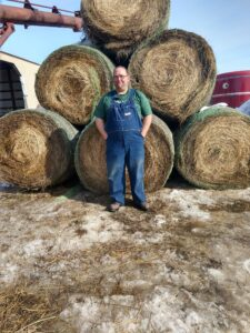 Brent Edington standing in front of bales of hay