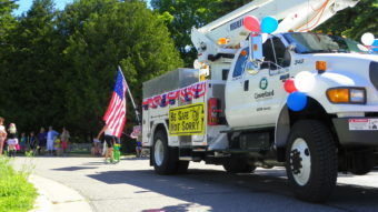 "Cloverland Electric truck in parade with sign ""Be Safe, Not Sorry"""