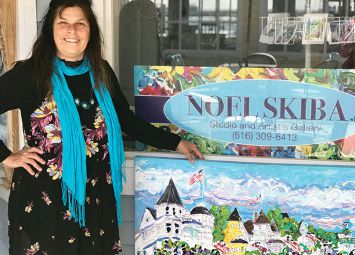 Noel Skiba standing outside her store with a painting.