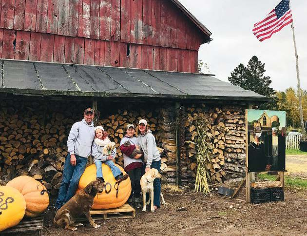 Andy, Jackie, Brady, and Emma Ditmyer sitting outside their barn with their dogs and pumpkins.