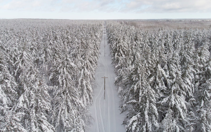 aerial view of snow covered forest with power poles