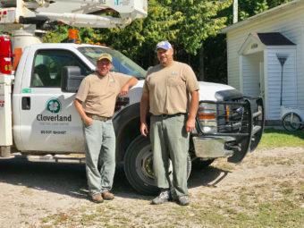 Linemen standing in front of Cloverland truck.