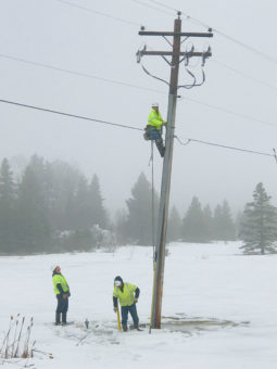 Linemen climbing power pole during winter in the snow.