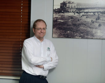 Mike Heise standing near photograph on wall.