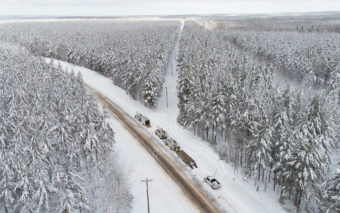 Aerial view of snow covered forest with roads with power lines in between, and electric service trucks on the roads.