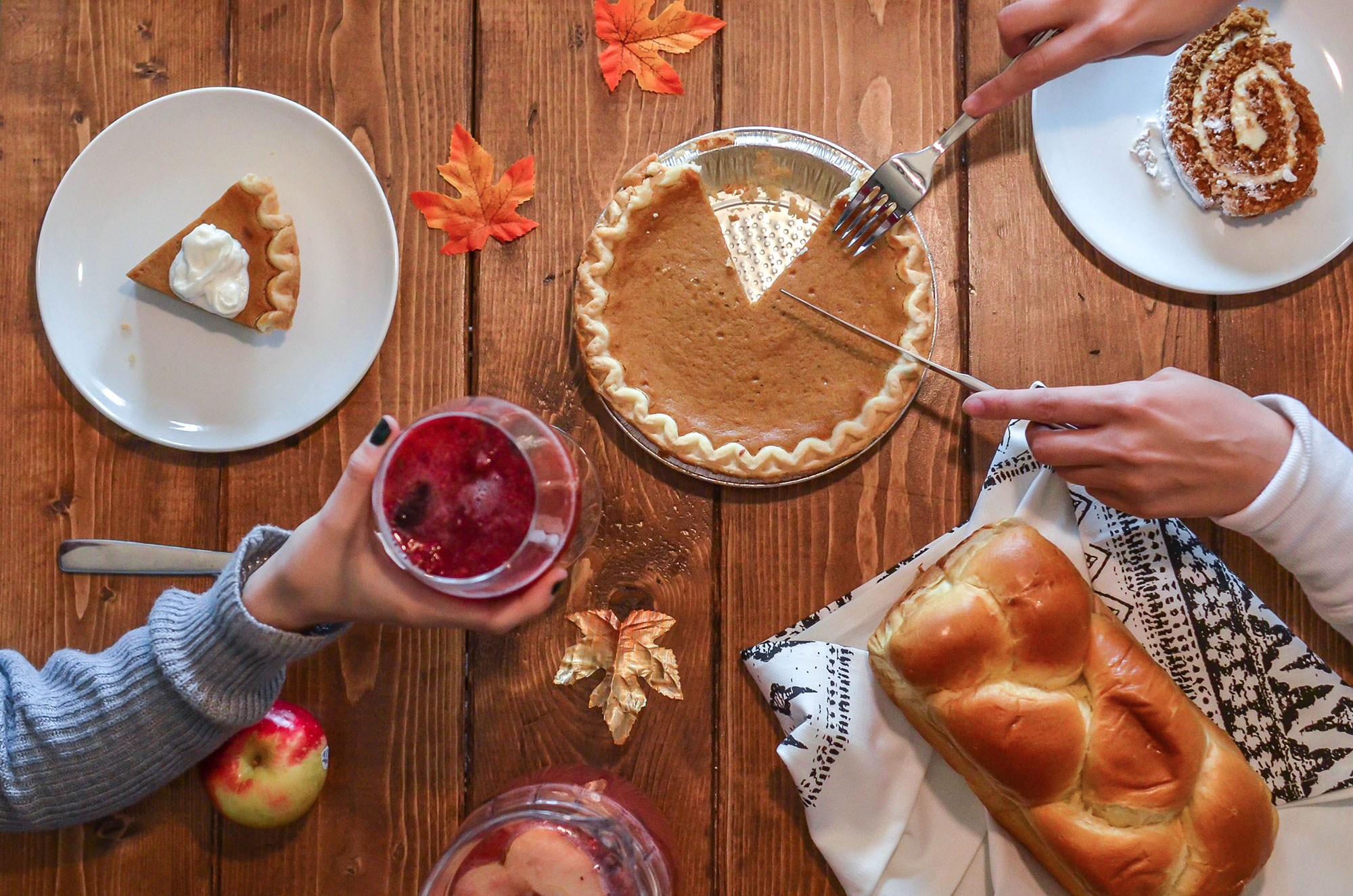 table with pumpkin pie, bread, apples, and leaves